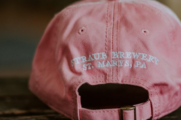pink baseball cap with Straub logo and pink ribbon