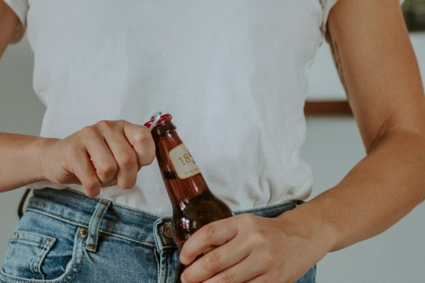 woman opening beer bottle with Straub bottle opener