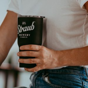 man holding black Straub travel mug