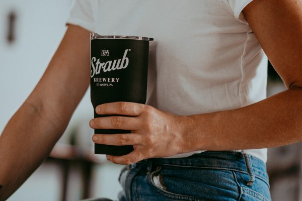 man holding black Straub travel mug